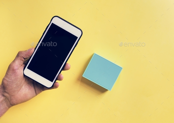 Hand holding smartphone and bluetooth speaker - Stock Photo - Images