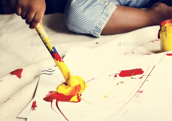 Black kid enjoying his painting - Stock Photo - Images