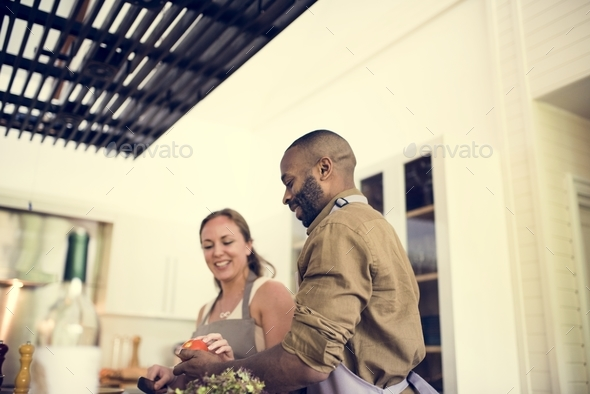 Couple cooking in a kitchen together - Stock Photo - Images