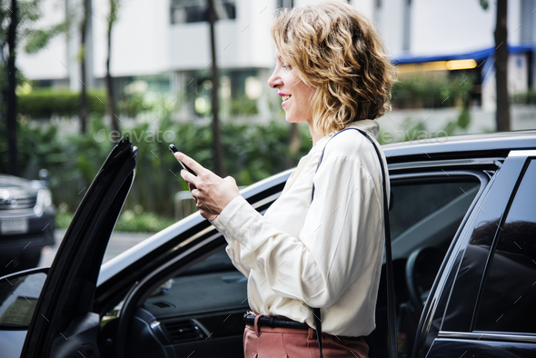 Woman texting before getting into the car - Stock Photo - Images