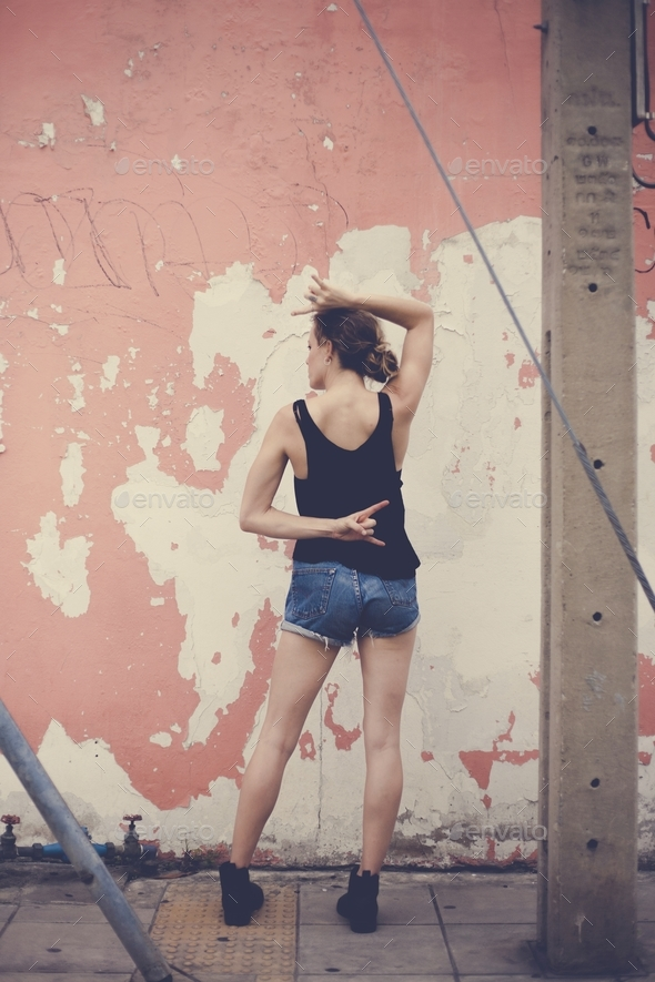 Young caucasian woman posing in front of the wall - Stock Photo - Images
