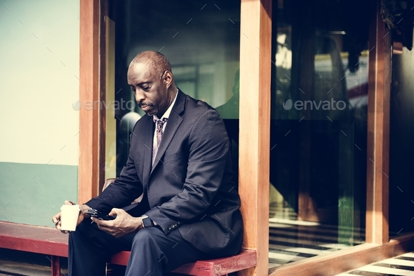 Businessman sitting alone working on phone - Stock Photo - Images