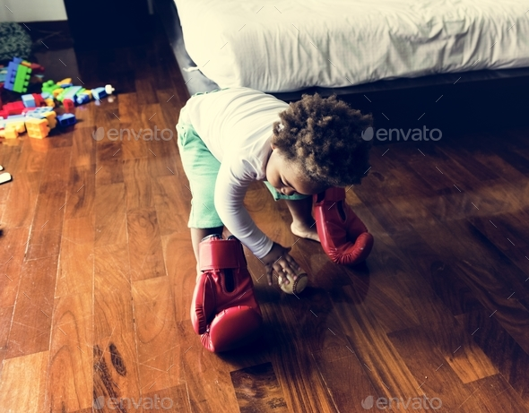 African descent kid with boxing glove on wooden floor - Stock Photo - Images