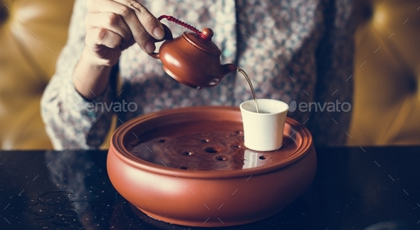 Woman pouring tea into a cup - Stock Photo - Images