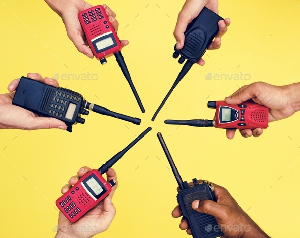 Group of hands holding portable two way radios with yellow background - Stock Photo - Images
