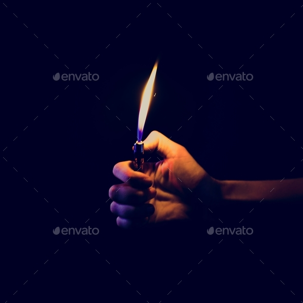 Hand holding a lit lighter in the dark - Stock Photo - Images