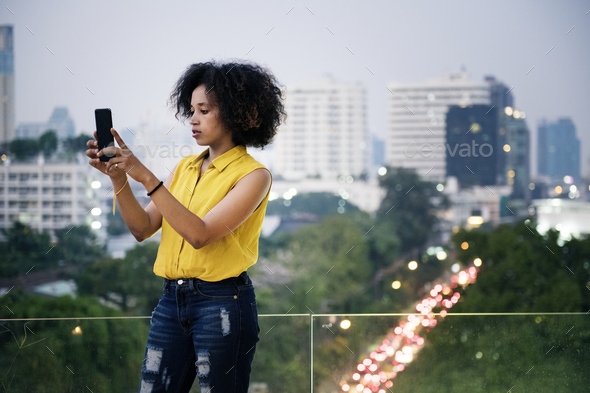 Young woman taking a photo in the cityscape - Stock Photo - Images
