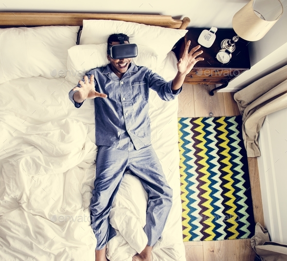 Man in bed using a VR headset - Stock Photo - Images