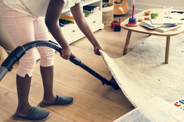 Young teen girl vacuuming up the house - Stock Photo - Images
