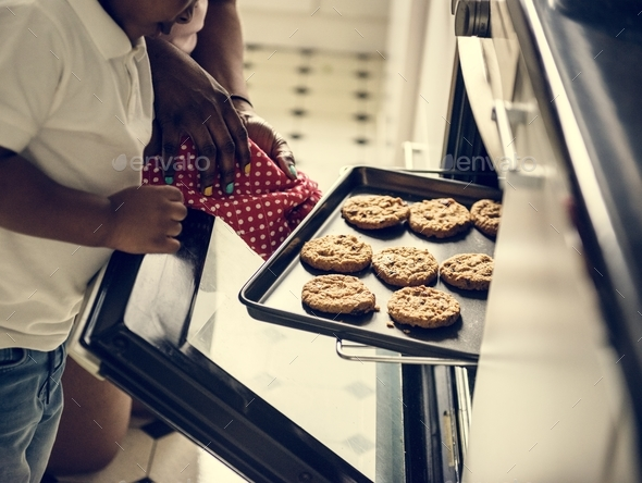 Black kid helping mom baking cookies in the kitchen - Stock Photo - Images