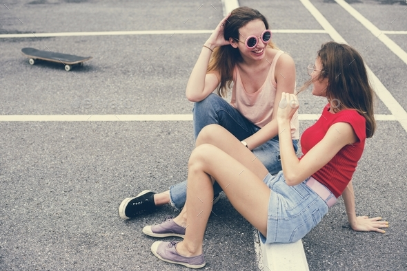 Woman friends sitting on the ground and talking together - Stock Photo - Images