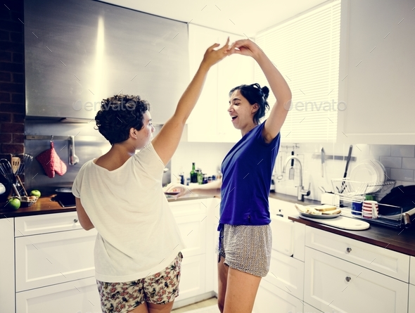 Lesbian couple dancing in the kitchen - Stock Photo - Images