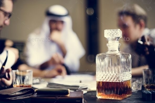 Whiskey decanter with business people in the background - Stock Photo - Images