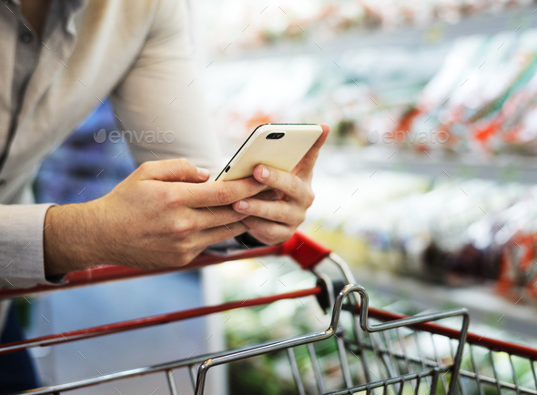 Man playing with his phone at supermarket - Stock Photo - Images