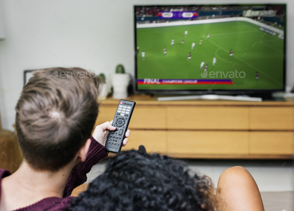 Couple watching a football game on TV - Stock Photo - Images
