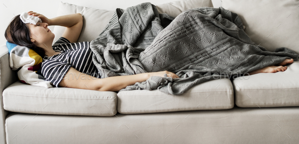 Woamn sick at home on the couch - Stock Photo - Images