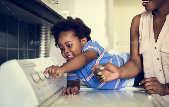 African descent kid helping mom doing the laundry - Stock Photo - Images
