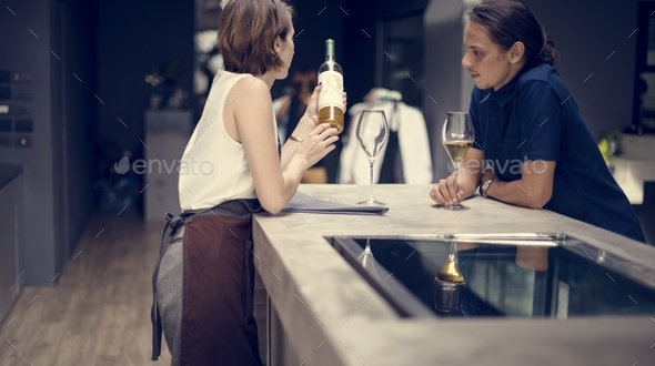 Bartender showing a wine to customer at the bar - Stock Photo - Images