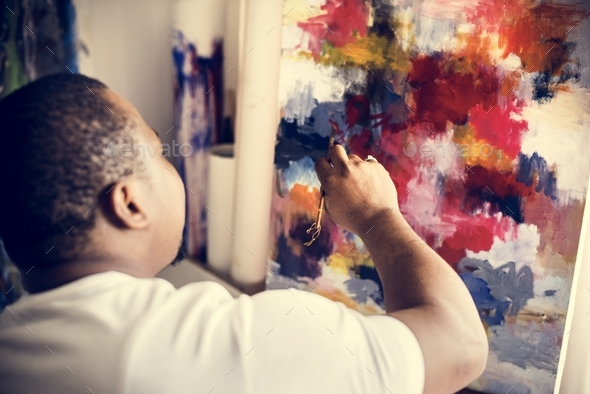 Black artist man doing his art work - Stock Photo - Images