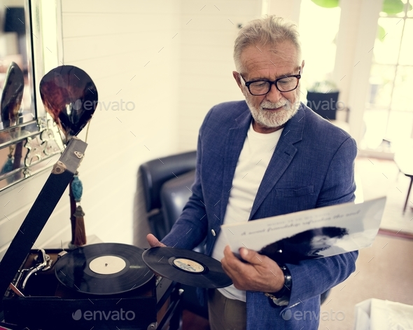 An elderly man playing a record - Stock Photo - Images