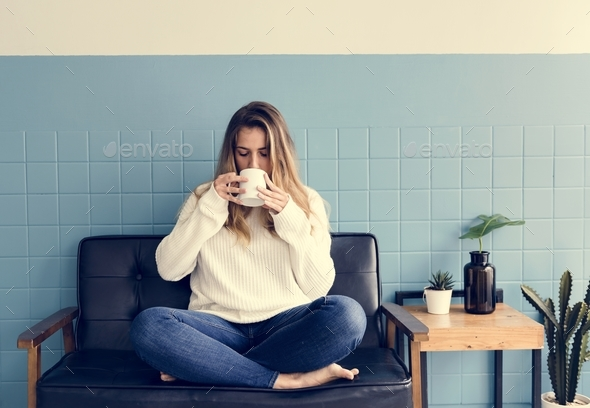 A Caucasian Woman Sitting and Drinking Coffee - Stock Photo - Images
