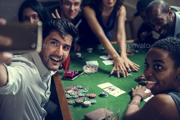 Group of people playing gamble in casino and taking selfie - Stock Photo - Images