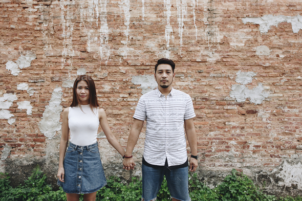 Asian couple holding hands together - Stock Photo - Images