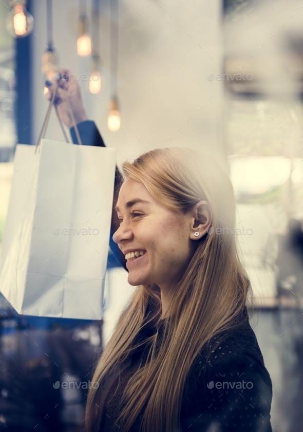 Caucasian girl smiling showing shopping bag - Stock Photo - Images