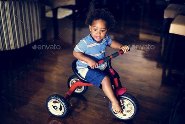 Black kid riding the bike in the house - Stock Photo - Images