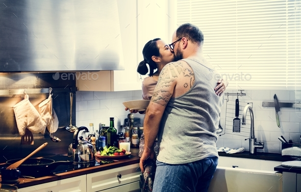 Wife kissing husband at the kitchen - Stock Photo - Images