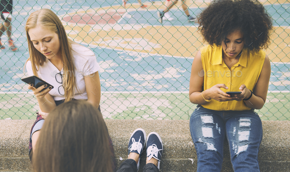Friends in the park using smartphones - Stock Photo - Images