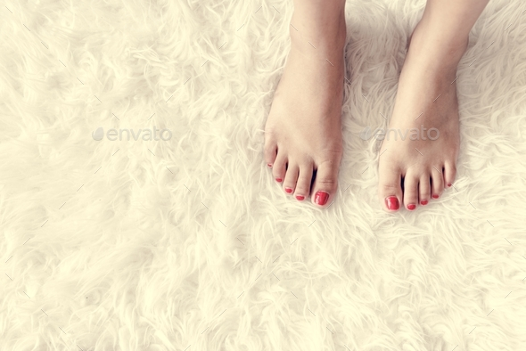 Closeup of woman legs on white fluffy carpet - Stock Photo - Images