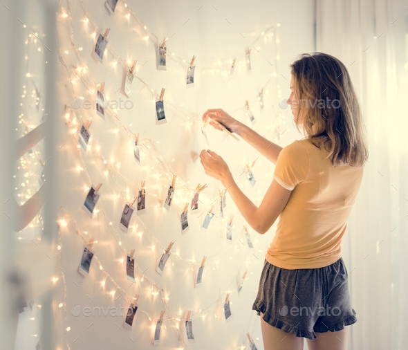 A woman looking at photos hanging on decoration lights - Stock Photo - Images