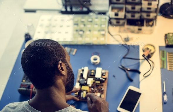 African ethnicity technician man working at his station - Stock Photo - Images