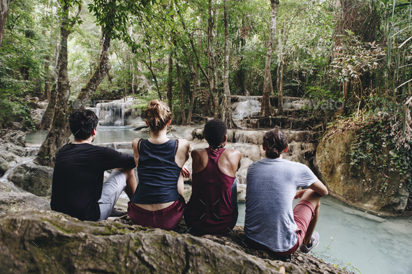 Friends hanging out by a waterfall in the jungle - Stock Photo - Images