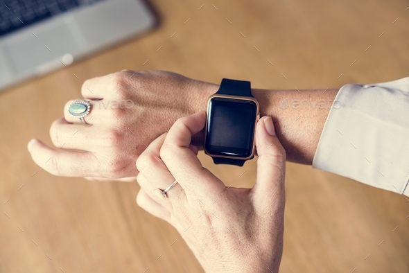 Hand setting a smartwatch on another hand - Stock Photo - Images