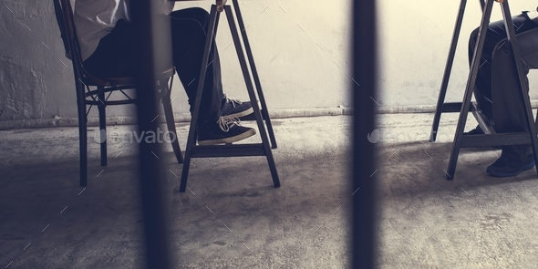 Closeup of pairs of legs in jail - Stock Photo - Images