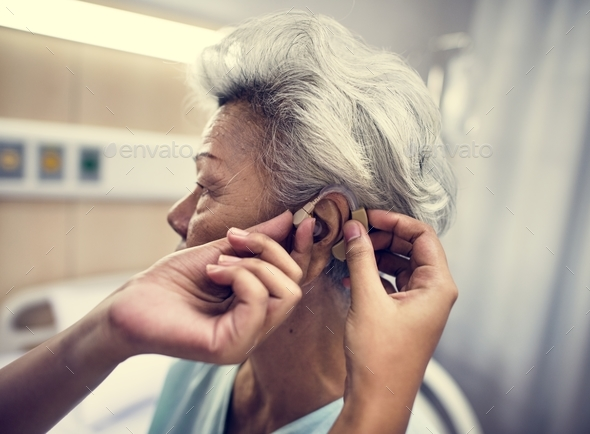 Asian old woman having her ears checked - Stock Photo - Images
