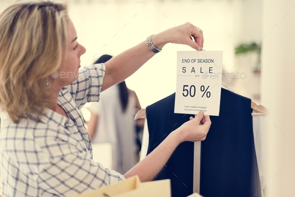 Woman checking out discounted clothes - Stock Photo - Images