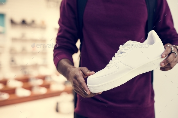 African man holding a white sneaker - Stock Photo - Images