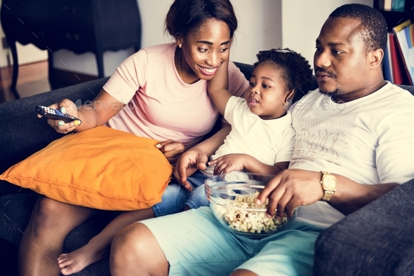 Black family eating popcorn while watching movie at home - Stock Photo - Images