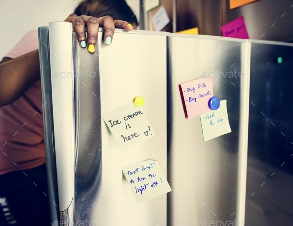 African descent woman opening the fridge - Stock Photo - Images