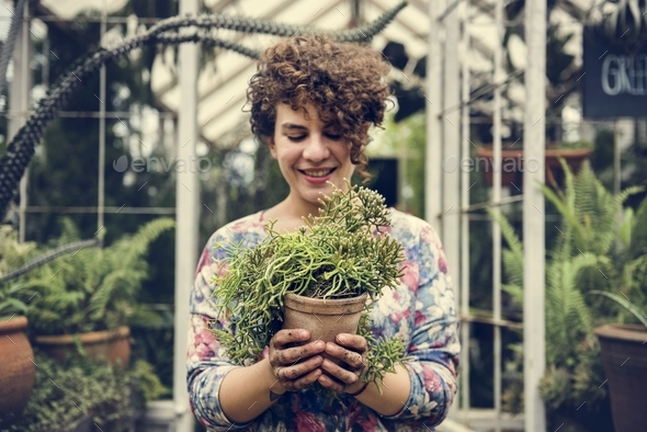 Woman holding a pot of plants - Stock Photo - Images