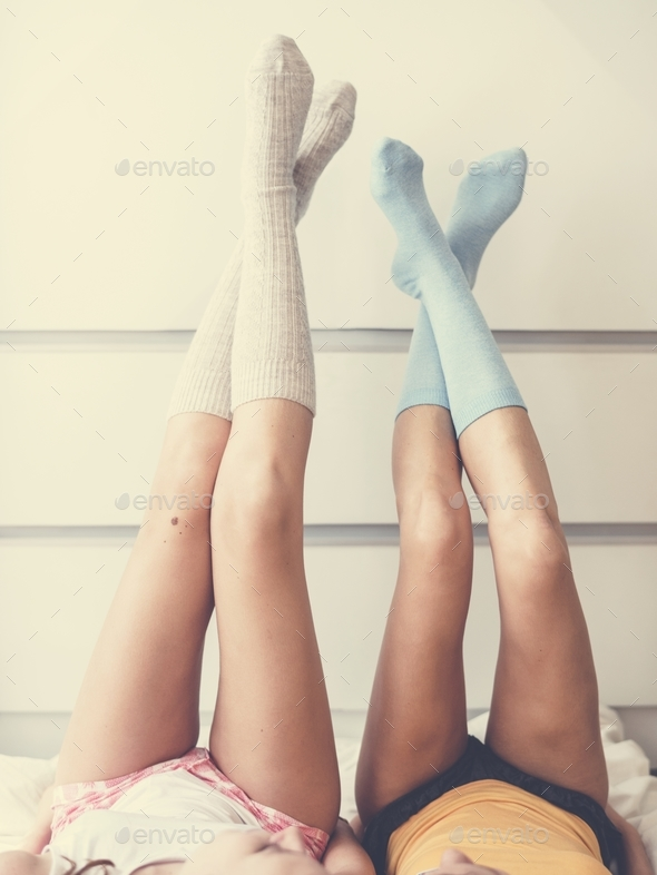 Women with their legs against the wall - Stock Photo - Images