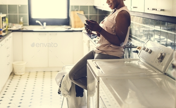 Black woman using digital tablet near the washing machine - Stock Photo - Images