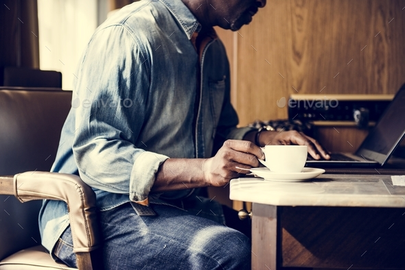 Man working on laptop and having a hot drink - Stock Photo - Images
