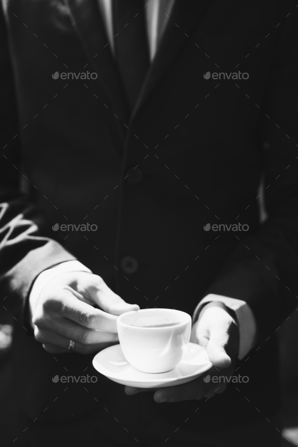Businessman holding coffee cup - Stock Photo - Images
