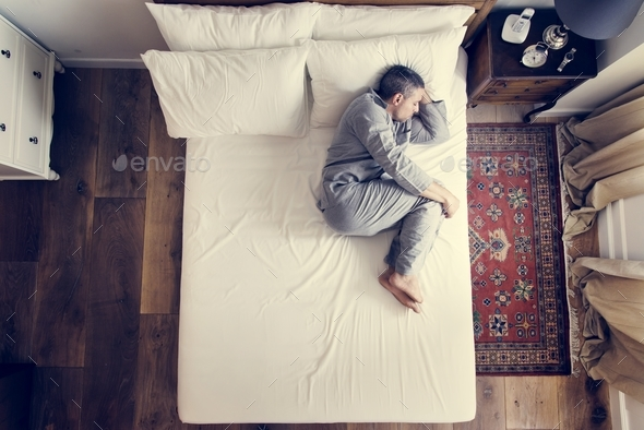 French man sleep alone on bed - Stock Photo - Images