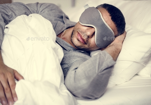A man sleeping on a bed - Stock Photo - Images