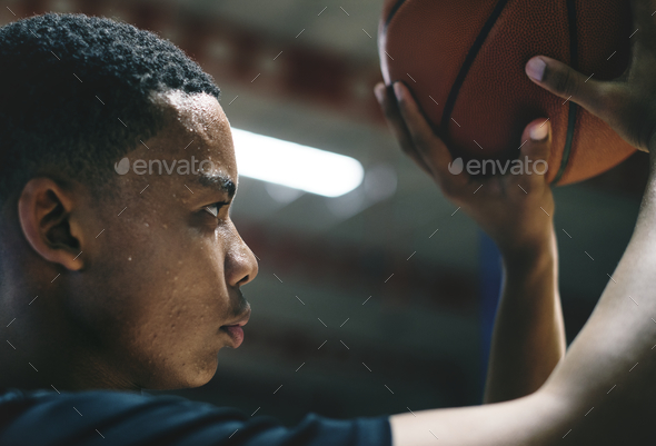 African American teenage boy concentrated on playing basketball - Stock Photo - Images
